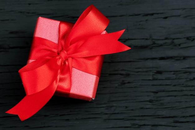 Geschenkbox rotes neues jahr oder weihnachten verpackter geschenkbehälter mit rotem band auf schwarzem holztisch