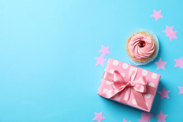Geschenkbox, sterne und cupcake auf blauem hintergrund, platz für text