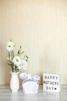 Geschenkbox trendy eingewickelt in seidenstoff in furoshiki-technik, lichtbox mit schriftzug happy mother's day, weiße blumen eustoma oder lisianthus in vase auf holztisch. zero waste life-konzept.