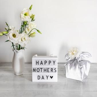 Geschenkbox trendy eingewickelt in seidenstoff in furoshiki-technik, lichtbox mit schriftzug happy mother's day