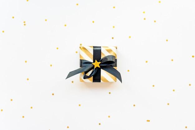 Geschenkbox über sternförmigen goldenen pailletten auf einem schwarzen hintergrund.