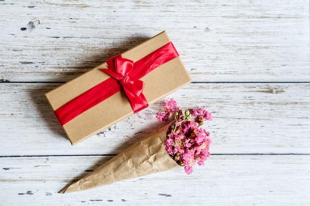 Geschenkbox und blumen auf holz