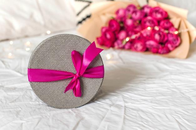 Geschenkbox und blumenstrauß auf dem bettkonzept des valentinstags-märz-geburtstagsgeschenks und anderer...