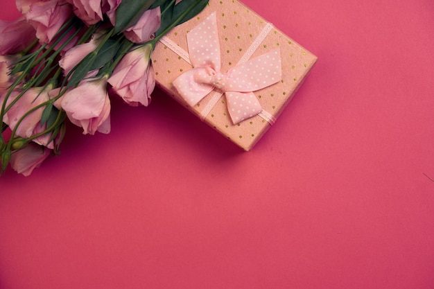 Geschenkbox und blumenstrauß auf rosa hintergrundbogenferien-draufsicht.