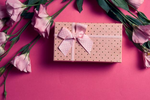 Geschenkbox und blumenstrauß auf rosa hintergrundbogenferien-draufsicht