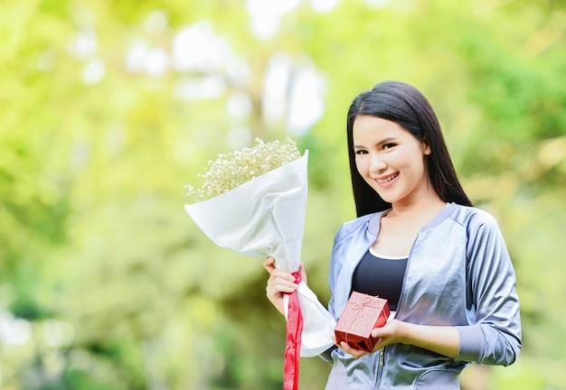 Geschenkbox und blumenstrauß des schönen lächelns des asiatischen mädchens der blumen in der hand geben ein geschenk für weihnachten und festival oder valentinstag des neuen jahres