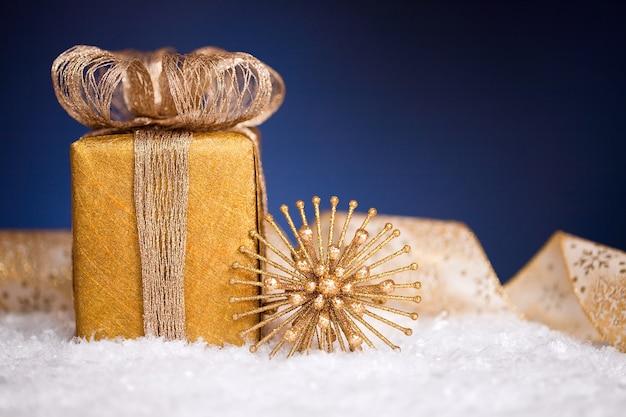Geschenkbox und christbaumschmuck im schnee auf blauem hintergrund