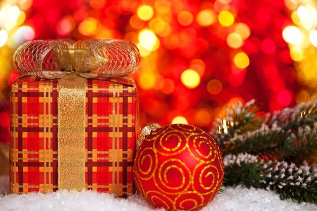 Geschenkbox und christbaumschmuck im schnee auf lichthintergrund