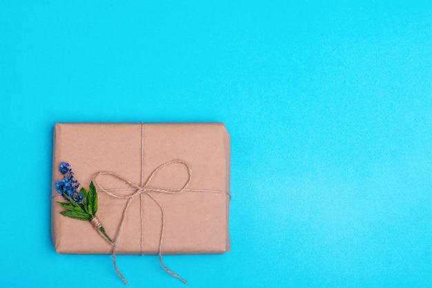 Geschenkbox und ein blumenstrauß von lavendel auf blauem hintergrund