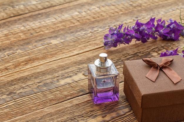 Geschenkbox und eine flasche parfüm auf holzbrettern mit lila blüten verziert. ansicht von oben.