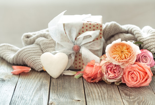 Geschenkbox und frische rosen auf hölzernem hintergrund