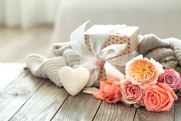 Geschenkbox und frische rosen zum valentinstag oder frauentag. urlaubskonzept.