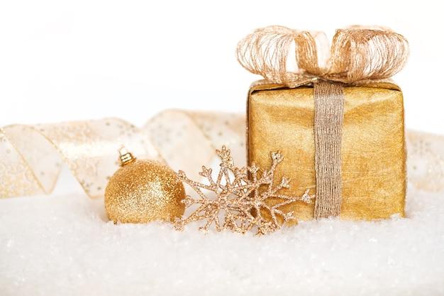Geschenkbox und goldschmuck im schnee auf weißem hintergrund. weihnachtskonzept. geringe schärfentiefe