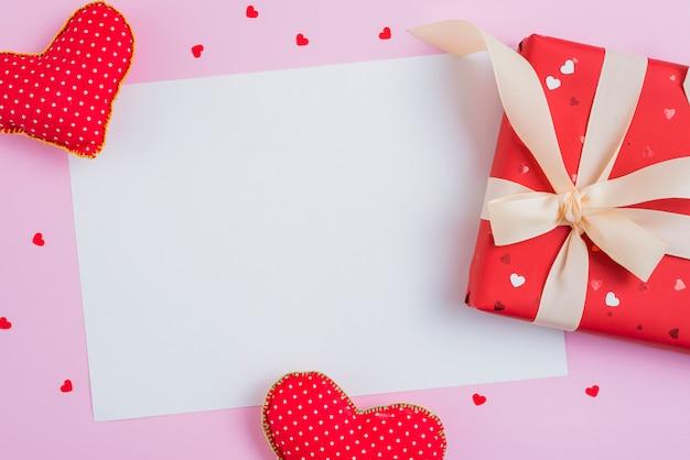 Geschenkbox und handgemachte herzen nahe papierblatt