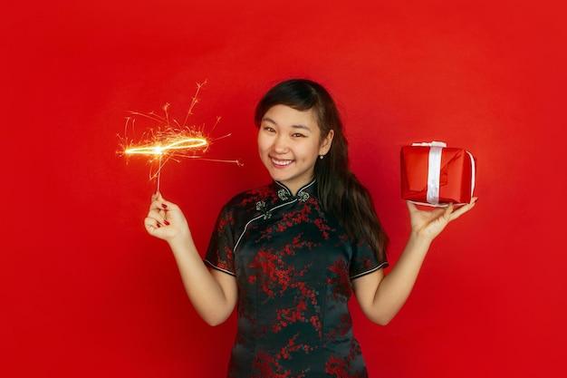 Geschenkbox und helle wunderkerze. frohes chinesisches neujahr. asiatisches junges mädchenporträt auf rotem hintergrund. weibliches modell in traditioneller kleidung sieht glücklich aus. copyspace.