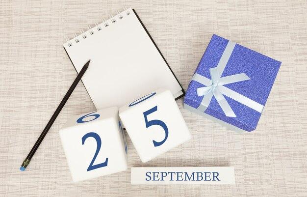 Geschenkbox und holzkalender mit trendigen blauen zahlen, 25. september