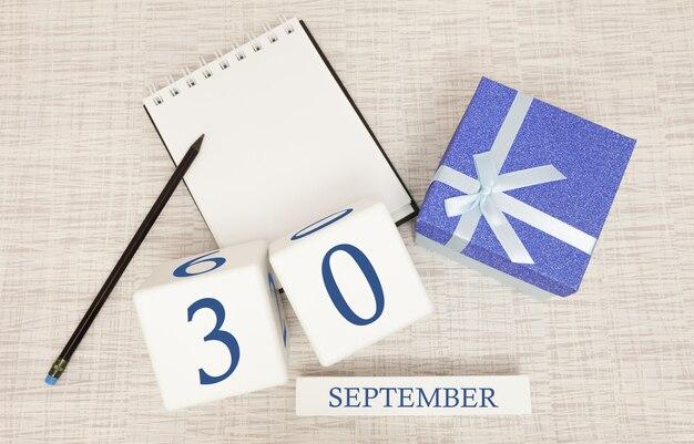 Geschenkbox und holzkalender mit trendigen blauen zahlen, 30. september