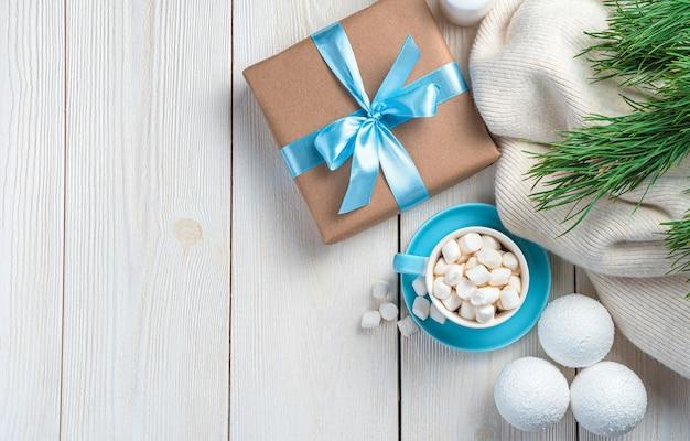 Geschenkbox und kaffee mit marshmallows auf hellem hintergrund mit tannenzweigen