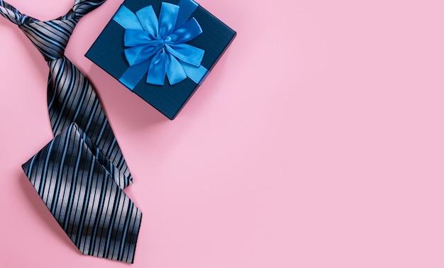 Geschenkbox und krawatte des glücklichen vatertags auf rosa wand. draufsicht.