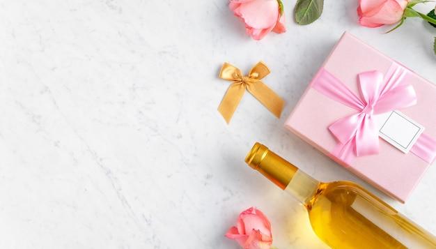 Geschenkbox und rosa rosenblume auf weißem marmor-tischhintergrund für valentinstag-feiertagsgeschenk-entwurfskonzept.