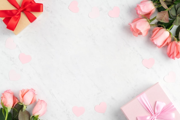 Geschenkbox und rosa rosenblume auf weißer marmor-tischoberfläche für muttertag-feiertagsgruß-entwurfskonzept.