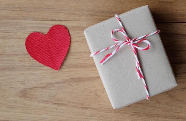 Geschenkbox und rote gewebeherzform auf hölzernem hintergrund