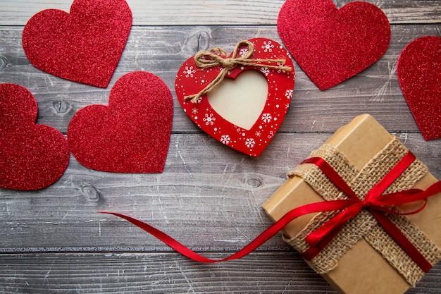 Geschenkbox und rote herzen auf hölzernem hintergrund