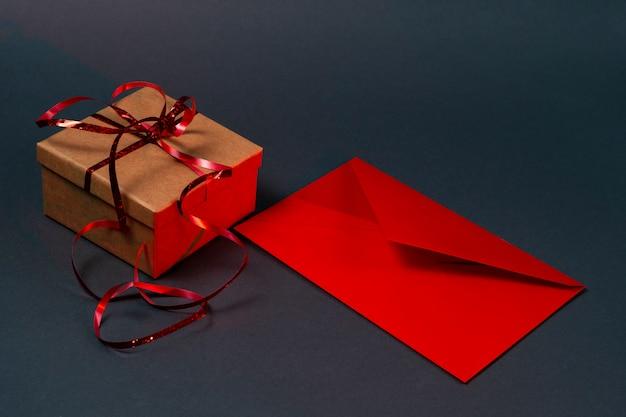 Geschenkbox und roter briefumschlag auf grau