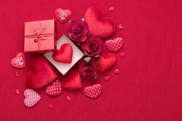 Geschenkbox und rotes herz stiegen auf stoffhintergrund mit kopienraum für liebeshochzeit oder valentinstag.