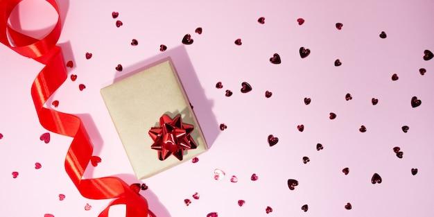 Geschenkbox und rotes satinband an der seite auf einem rosa hintergrund. kleine rote herzen sind verstreut. freier platz für text. geschenkkonzept, feiertage, liebe, valentinstag.