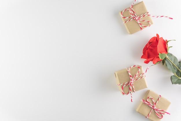 Geschenkbox und rotrosenblume lokalisiert auf weißem hölzernem beschaffenheitshintergrund