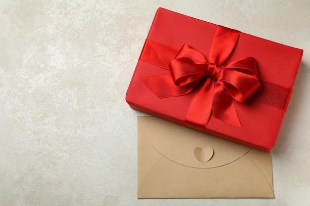 Geschenkbox und umschlag auf weißem strukturiertem hintergrund