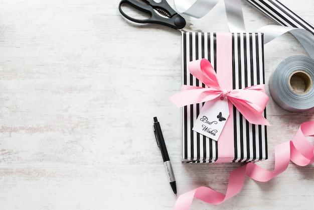 Geschenkbox und verpackungsmaterialien auf einem weißen hölzernen alten hintergrund