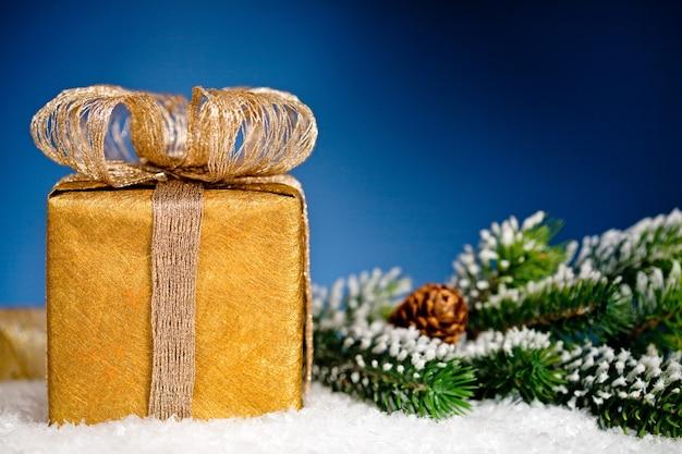 Geschenkbox und weihnachtsbaumast im schnee auf blauem hintergrund. winterferienkonzept