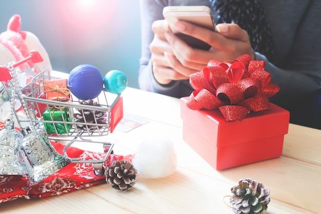 Geschenkbox und weihnachtsverzierung auf tabelle mit der frau, die handy verwendet