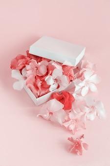 Geschenkbox voller blumen über einem rosa hintergrund schließen