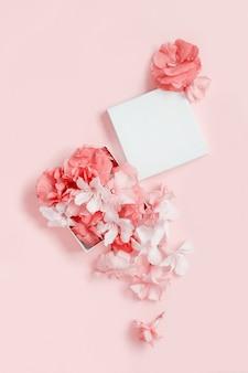 Geschenkbox voller blumen über einer rosa hintergrundoberansicht