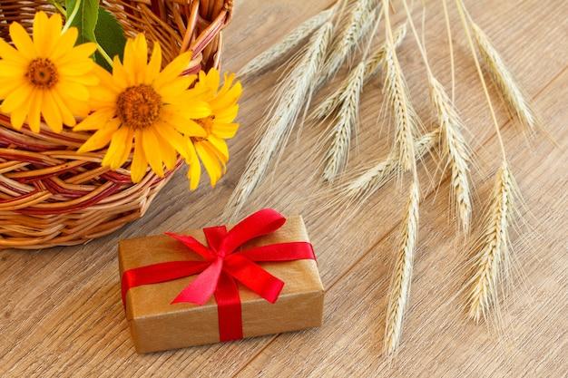 Geschenkbox, weidenkorb mit blumen und ährchen aus weizen auf holzbrettern. ansicht von oben.
