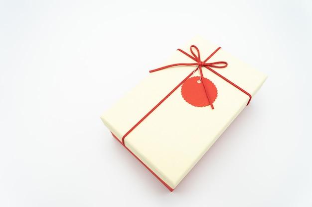 Geschenkbox weiß mit einem roten seil, das aus einem hohen winkel um die ecke gewickelt ist