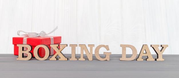 Geschenkbox wird mit einem band mit wörtern boxing day auf hölzernem weißem hintergrund gebunden