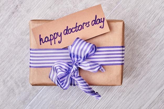 Geschenkbox zum tag des doktors. grußkarte und bogen. herzlichen glückwunsch zum arzt.