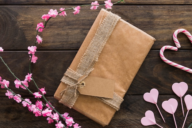 Geschenkbox zwischen zweigen mit blumen und zuckerstangen