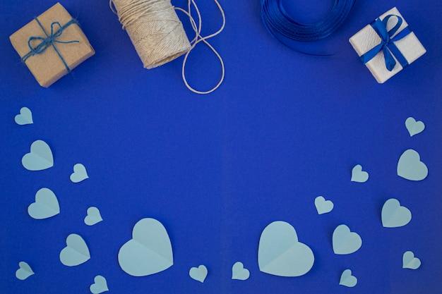 Geschenkboxbögen, bänder auf dunkelblauem hintergrund. valentinstag. trendfarben. das konzept des valentinstags. draufsicht, copyspace