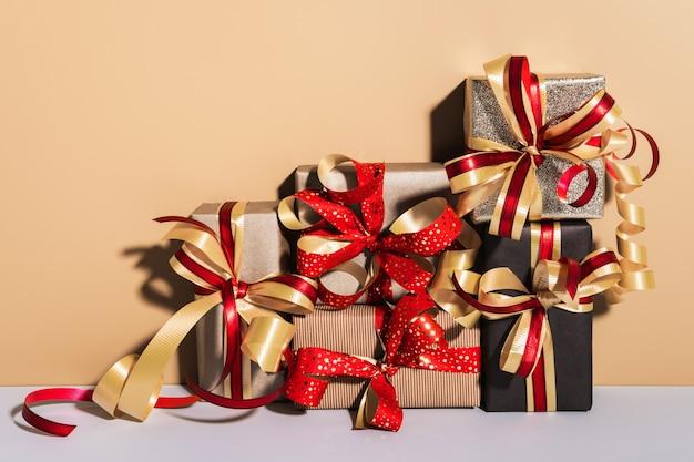 Geschenkboxen auf beige grauem hintergrund. geschenke verpackt in kraftpapier mit band und schleife. feiertags-shopping-konzept.