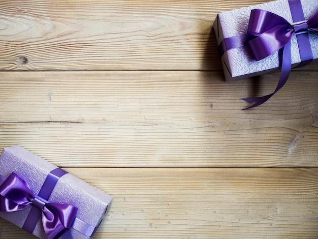 Geschenkboxen auf dem hintergrund des hölzernen brettes