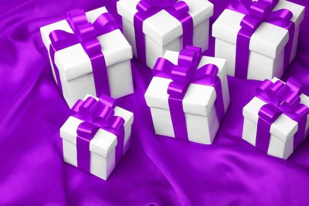 Geschenkboxen auf einem lila satinhintergrund