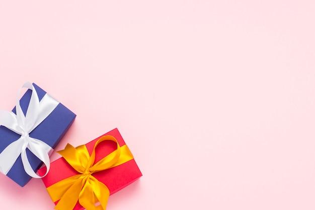 Geschenkboxen auf einem rosa hintergrund. urlaubskonzept