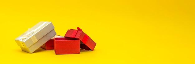Geschenkboxen auf gelbem hintergrund, banner. rote geschenkboxen, offene box. postkarte zum drucken, banner mit platz für text. panoramafoto, groß, leerer platz für glückwünsche oder design
