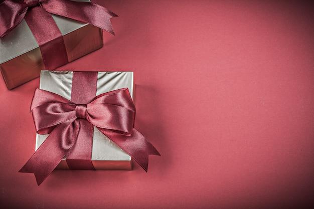 Geschenkboxen auf horizontalem bildfeiertagskonzept des roten hintergrunds