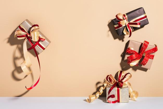 Geschenkboxen auf wandboden hintergrund. geschenke verpackt in kraftpapier mit band und schleife. feiertags-shopping-konzept.